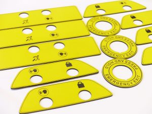 Laser raster engraved and cut yellow plastic laminate signage for modified vehicles.